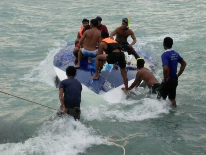 Thai locals clamber on top of the speedboat after it capsized near Koh Samui