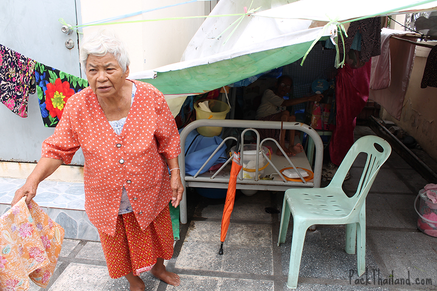 Two elderly women sleeping in a make-shift home inside the temple grounds