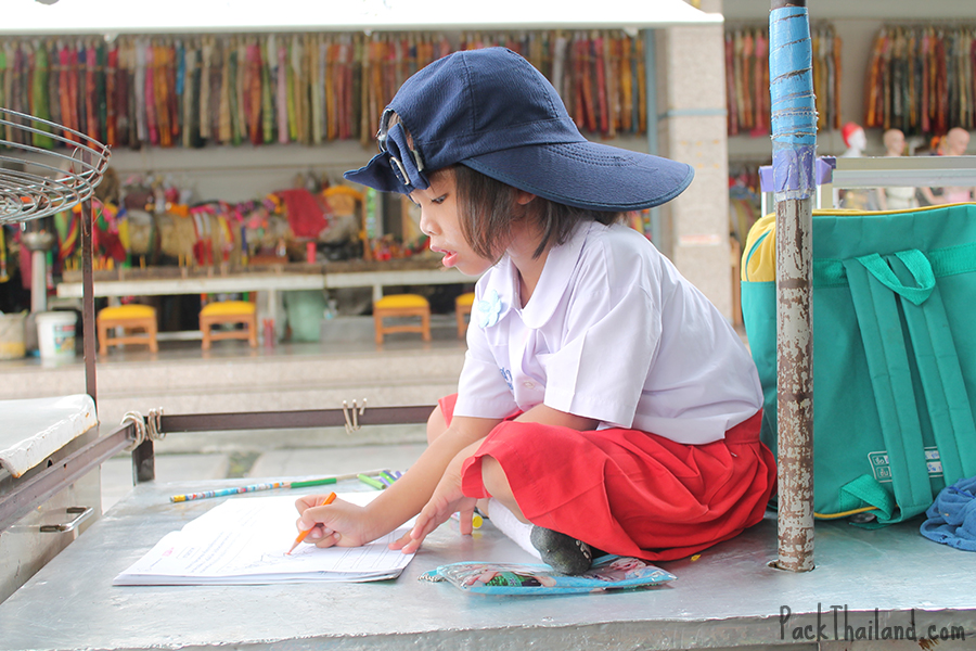 A young girl sits on her mother's food cart to do her homework