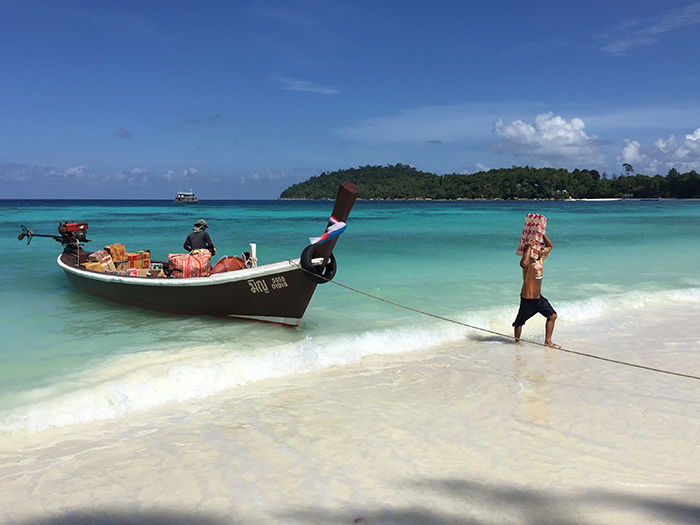 A worker loads supplies from a boat on a quiet, and clear, sunny day in June... perhaps the best time to visit Koh Lipe