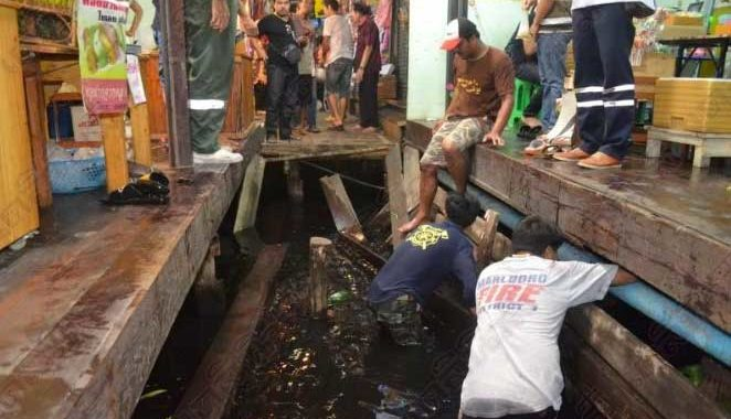 Thai men look for valuables in the water after the wooden walkway collapsed at Bang Plee market