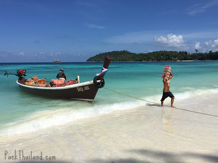 A young Thai man unloads supplies from a longtail boat on Koh Lipe Pattaya Beach for some of the island's boats and restaurants