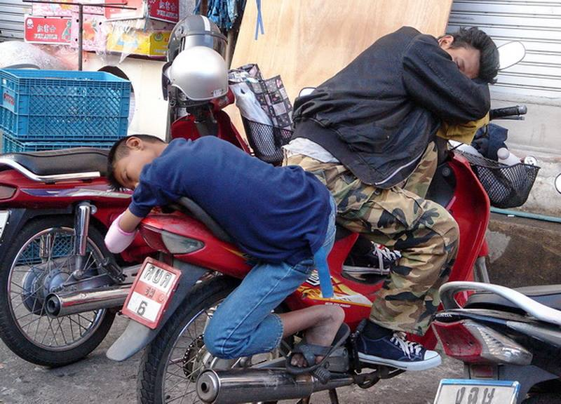 Two Thais sleeping on a moped