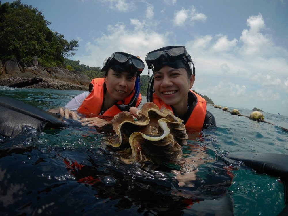 The two Chinese tourists smile as they hold a clam plucked from the sea bed on Koh Chang, Thailand