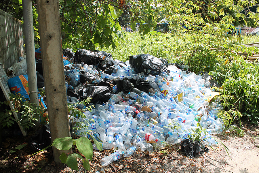 A pile of plastic water bottles left by a path