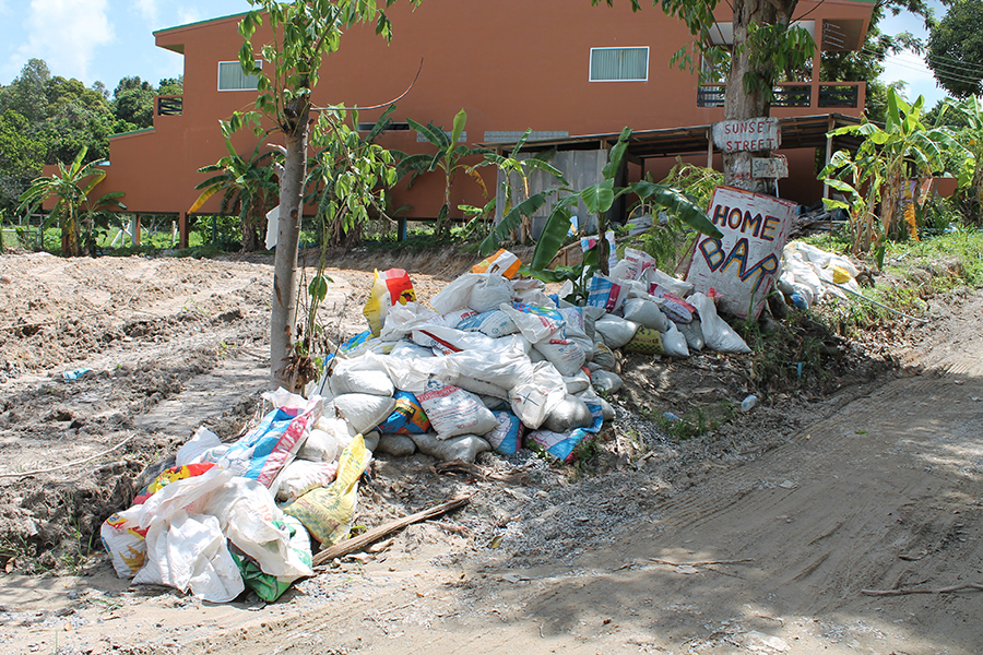 A pile of rubbish next to a sign for Home Bar