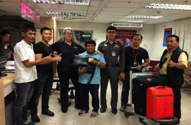 Suzanne Jones with the taxi driver, centre, and staff at Suvarnabhumi Airport in Bangkok after being reunited with her bag