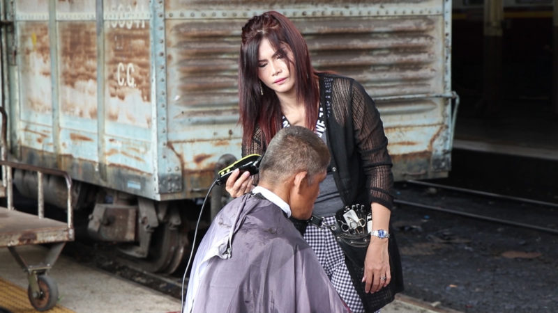 A hairdresser cuts a man's hair at the Hua Lamphong train station