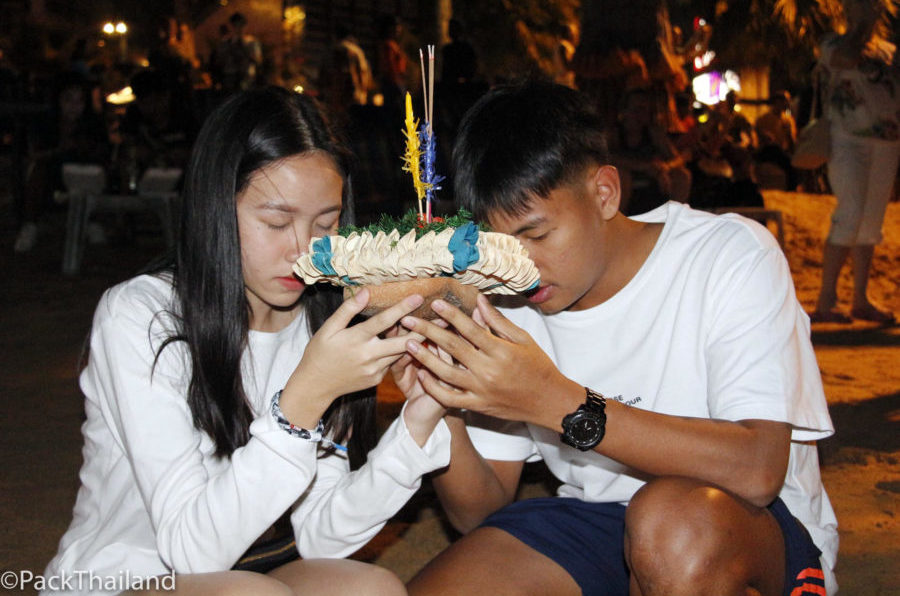 Two people pray as they prepare to release flowers into the sea during the Loi Krathong festival in Pattaya on November 3, 2017