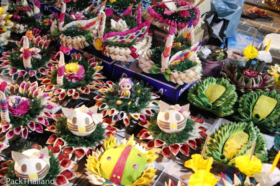 A stall with some decoratively arranged flower baskets and candles for floating out into the sea during Loi Krathong 2017